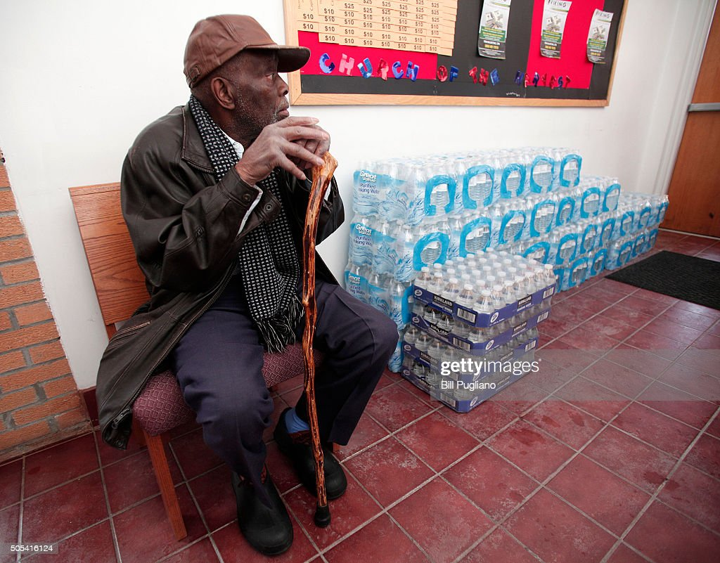 A man sits next to a stack of bottled water at a rally where the Rev Jesse Jackson spoke about the water crises at the Heavenly Host Baptist Church...