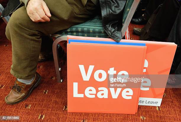 A man sits next to campaign placards as Boris Johnson delivers a speech speech at a 'Vote Leave' rally at the Centre for Life on April 16 2016 in...