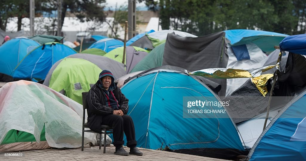 A man sits next to tents at a makeshift camp for migrants and refugees near the village of Idomeni not far from the Greek-Macedonian border on May 4, 2016. Some 54,000 people, many of them fleeing the war in Syria, have been stranded on Greek territory since the closure of the migrant route through the Balkans in February. / AFP / TOBIAS