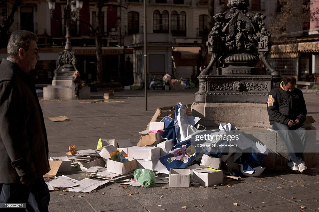 A man sits next to uncollected rubbish on a square of Granada on January 11, 2013. Rubbish collectors have been on strike in the municipality of Granada to protest against the austerity cuts imposed by the town hall. AFP PHOTO / JORGE GUERRERO
