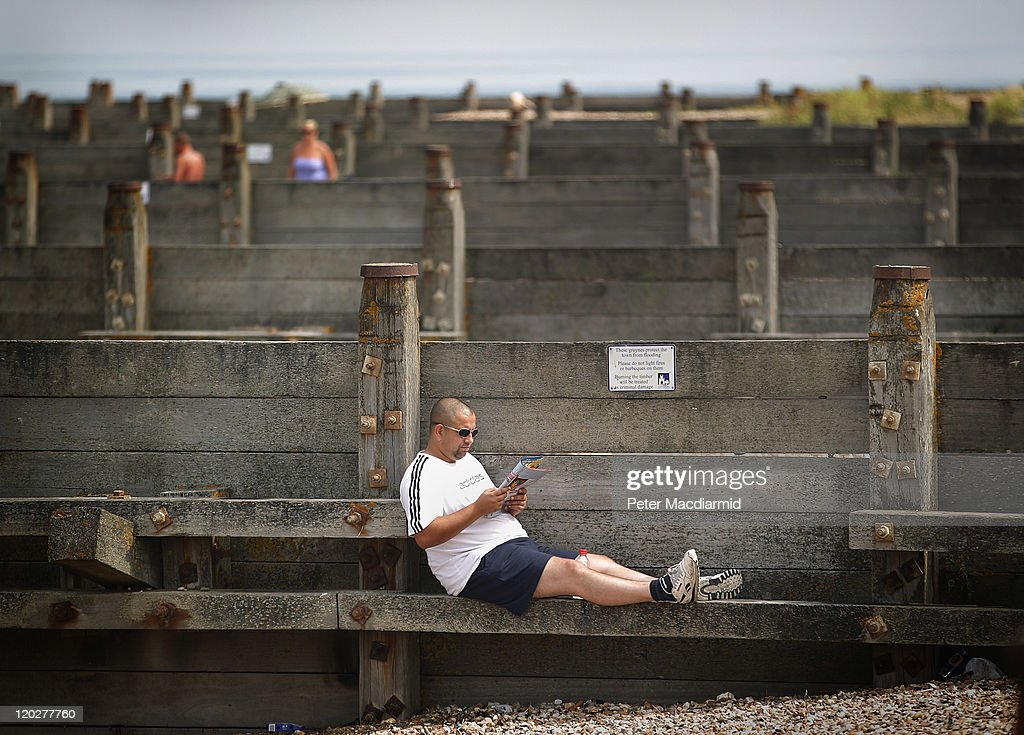 A man sits on a beach groyne reading a book on August 3, 2011 in Whitstable, England. Parts of southern England are experiencing high summer temperatures.