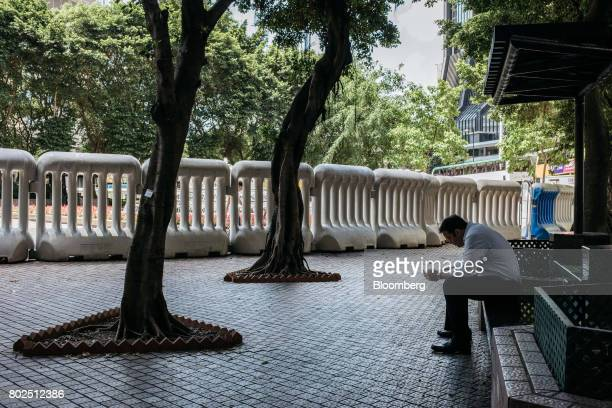 A man sits on a bench near water barricades near the Hong Kong Convention and Exhibition Center ahead of Chinese President Xi Jinping's arrival in...