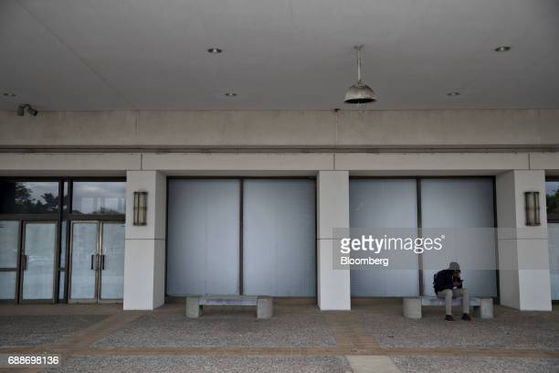 A man sits on a bench next to the recently shuttered Macy's Inc department store at the Neshaminy Mall in Bensalem Pennsylvania US on Saturday May 20...