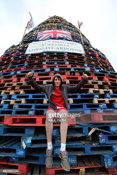 A man sits on a bonfire on the lower Shankill area of Belfast Northern Ireland ahead of the traditional 11th night bonfires on July 11 2015 The...