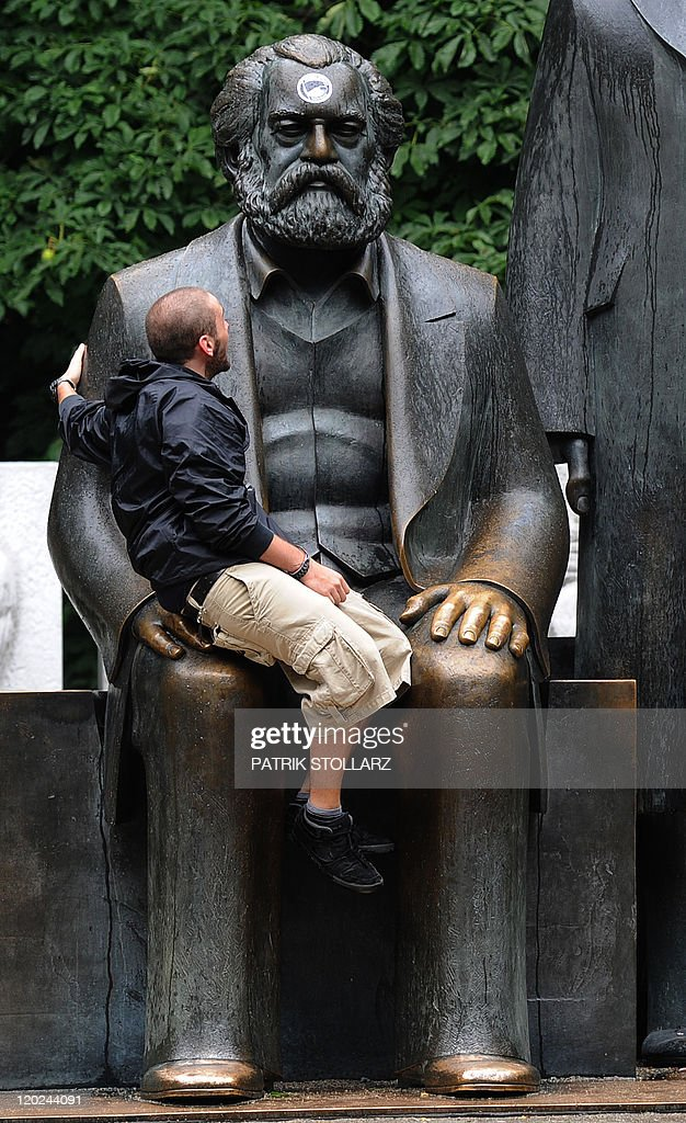 A man sits on a bronze statue of German philosopher, sociologist and economic historian Karl Marx on July 28, 2011 in Berlin. The monument, which also includes a statue of German industrialist and social scientist Friedrich Engels, has become an icon of the early communism ideology. It was built by east German sculptor Ludwig Engelhardt and inaugurated in 1986.