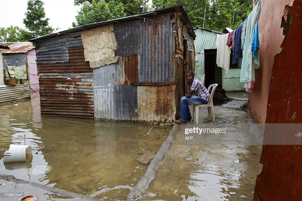 A man sits on a chair outside his house in a flooded area of Santo Domingo, on July 11, 2013 after Tropical Storm Chantal lashed the impoverished Caribbean island of Hispaniola -- shared by Haiti and the Dominican Republic. A firefighter was killed and more than 6500 people were evacuated in the Dominican Republic as Chantal has now weaken into a 'tropical wave'. AFP PHOTO/Erika SANTELICES