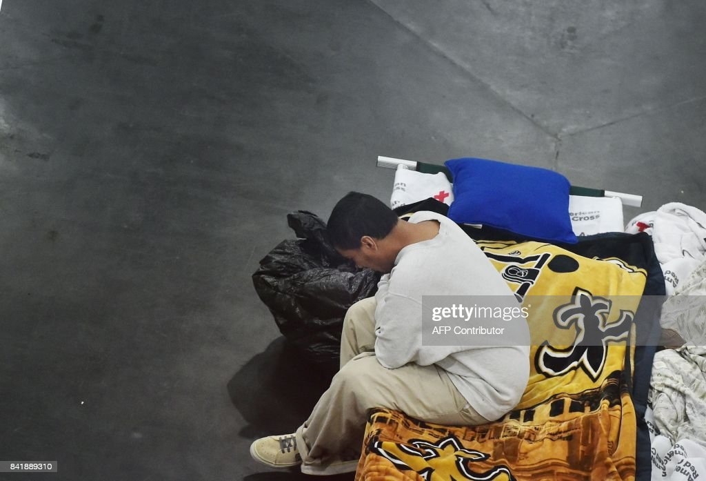 A man sits on a cot in the George R. Brown Convention Center which has been a shelter for evacuees from Hurricane Harvey in Houston on September 2, 2017. One week after Harvey blasted into southeast Texas as a Category Four hurricane, rescuers were still searching by air and by boat for people trapped in flooded homes. /