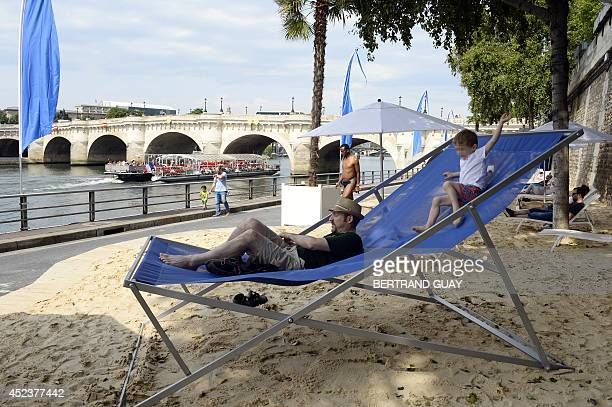 A man sits on a giant deckchair as a child plays on July 19 2014 on the opening day of the 13th edition of ParisPlages a temporary artificial beach...