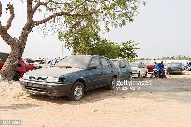 A man sits on a motor bike at the car park at the exit of Cotonou on January 12 2017 Benin's car market began its free fall last year while the...