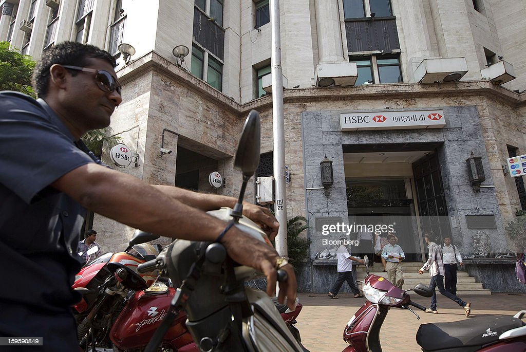 A man sits on a motorcycle in front of an HSBC Holdings Plc bank branch in Mumbai, India, on Wednesday, Jan. 16, 2013. India's financial system has been made vulnerable by a deterioration in bank assets and a lack of capital as the economy slowed, according to the International Monetary Fund. Photographer: Kuni Takahashi/Bloomberg via Getty Images