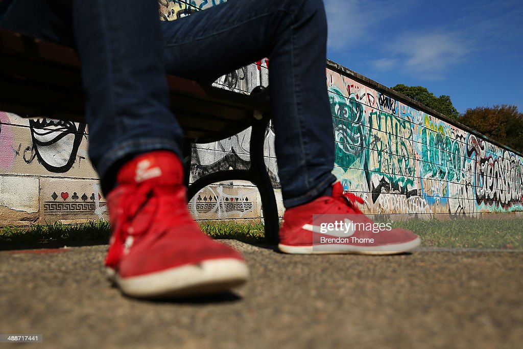 A man sits on a park bench in front of a wall strewn with graffiti on May 8, 2014 in Sydney, Australia. The Grafitti Control Amendment Act passed in the NSW legislative council yesterday includes tougher penalties a the ability for local courts to enforce community clean up duty on offenders.