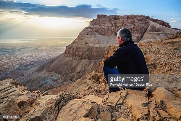 A Man Sits On A Rock Looking Out Over The Judean Desert