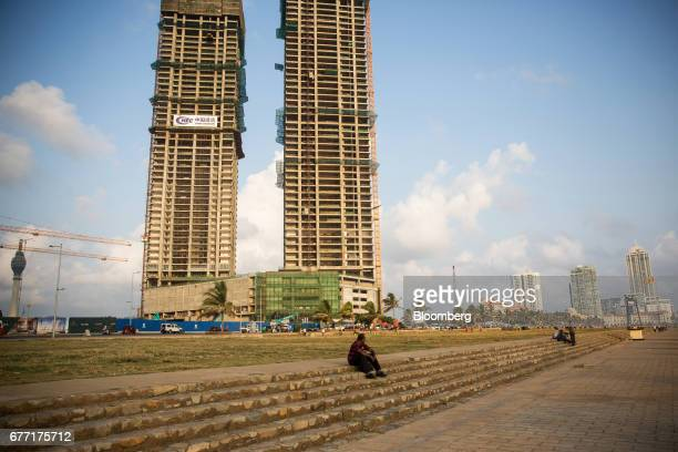 A man sits on a set of steps at Galle Face Green as the under construction ShangriLa Hotel Colombo stands in the background in Colombo Sri Lanka on...