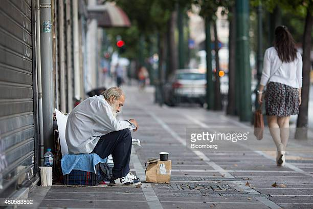 A man sits on a street and asks for money from pedestrians in Athens Greece on Monday July 13 2015 Greece has been in financial limbo since the...