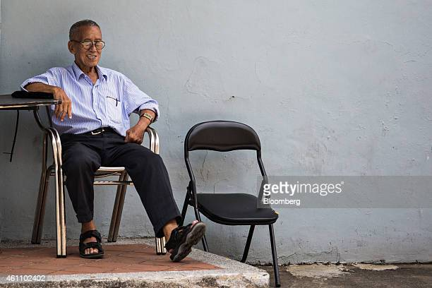 A man sits on a street in the area of Chinatown in Singapore on Tuesday Jan 6 2015 In a culture that traditionally expects children to look after...