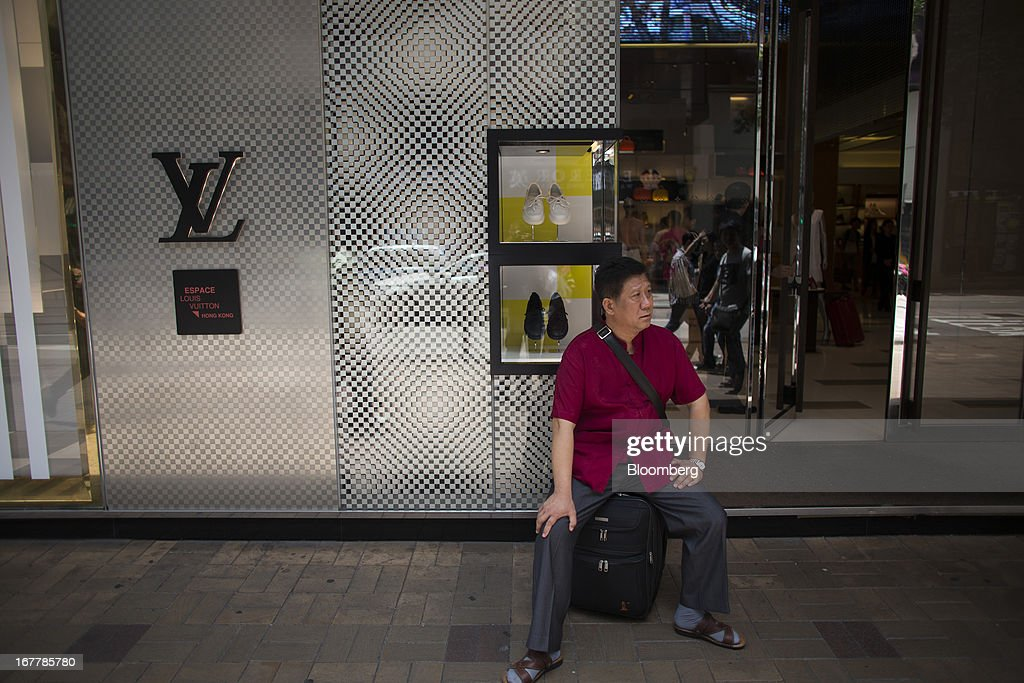 A man sits on a suitcase outside a Louis Vuitton store, operated by LVMH Moet Hennessy Louis Vuitton SA, in the Tsim Sha Tsui area of Hong Kong, China, on Tuesday, April 30, 2013. Financial Secretary John Tsang on Feb. 27 projected annual growth of 1.5 percent to 3.5 percent this year following 2012's 1.4 percent, the weakest rate since 2009 as Europe's sovereign debt crisis sapped global demand. Photographer: Lam Yik Fei/Bloomberg via Getty Images