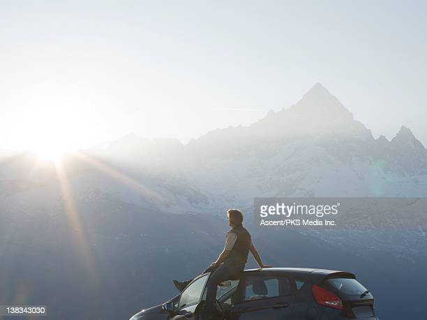 Man sits on car, watching sunsrise over mountains