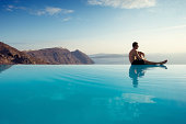 Man Sits on Edge of Infinity Pool in Santorini