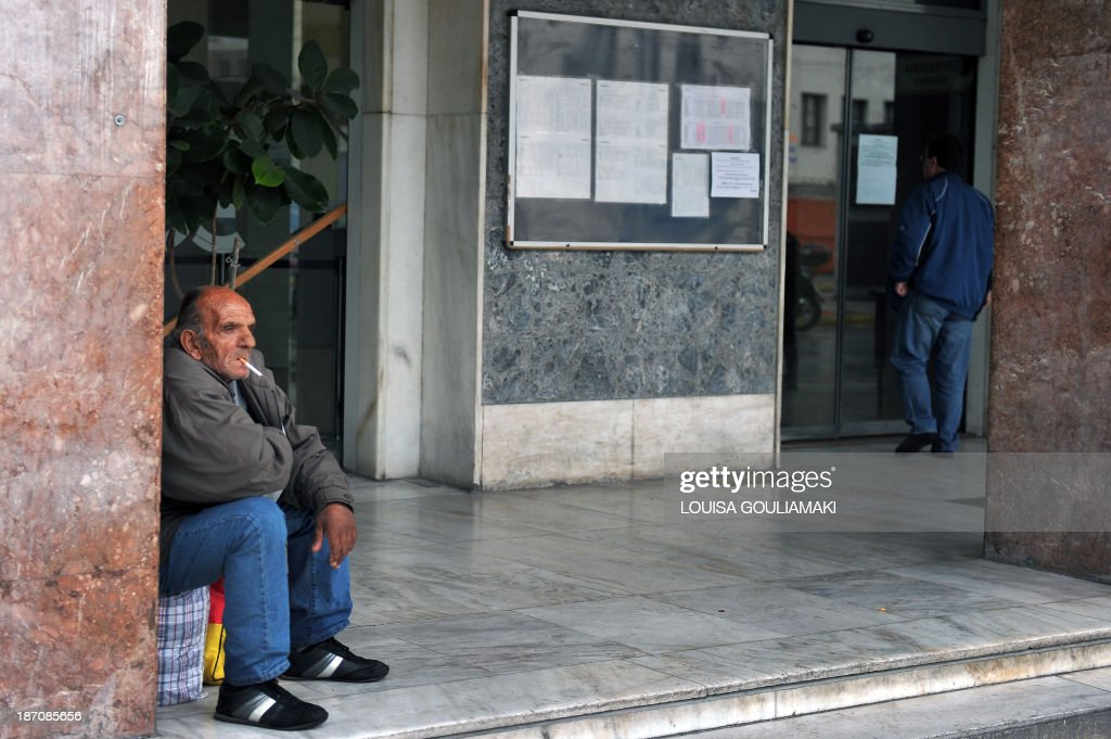 A man sits on his luggage at a closed railway station in Athens on November 6, 2013 during a 24-hour strike. A general strike hit Greece on November 6, paralyzing public services and disrupting transport as EU-IMF auditors worked to finalize the recession-hit country's next budget, looking to eliminate a fiscal shortfall that could bring more unpopular cuts. AFP PHOTO / LOUISA GOULIAMAKI