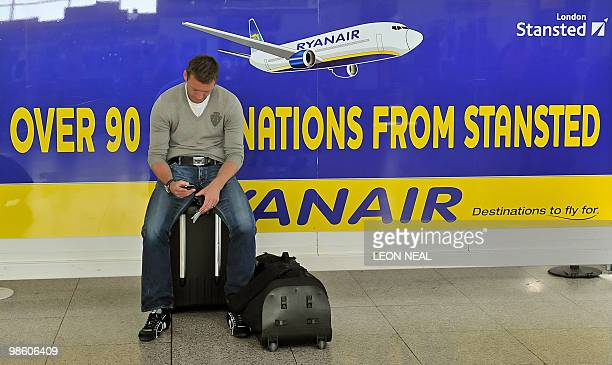 A man sits on his luggage beside a poster for Irish lowcost airline Ryanair in the departures area of Stansted airport in Essex on April 22 2010...