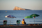 A man sits on Levante Beach in the early morning on August 10 2013 in Benidorm Spain Benidorm is one of Europe's top package holiday destinations and...