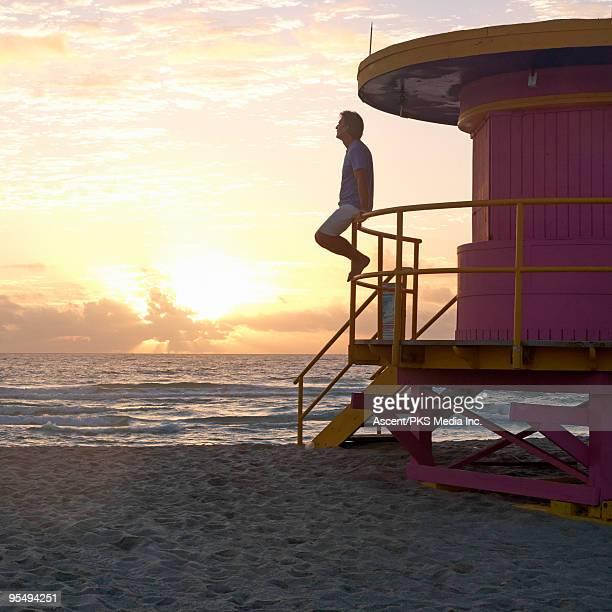 Man sits on lifeguard station railing, above beach