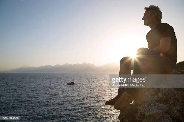 Man sits on rock above sea, looks off sunrise