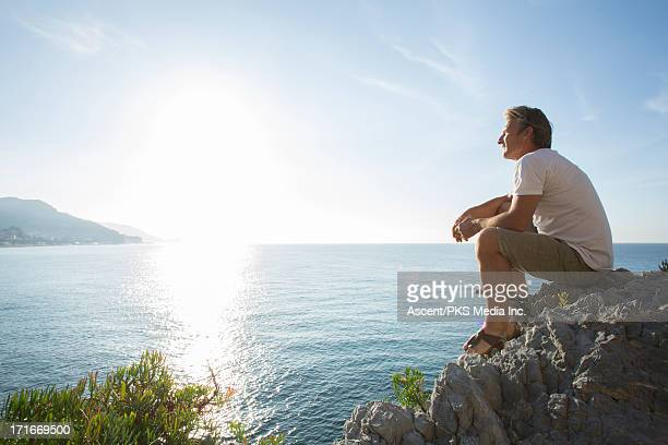 Man sits on rock above sea, looks out