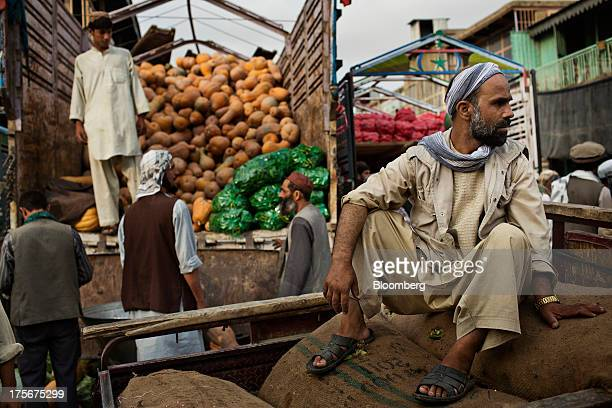 A man sits on sacks of produce as workers unload pumpkins from a truck at the Fresh Fruit And Vegetable National Market in Kabul Afghanistan on...