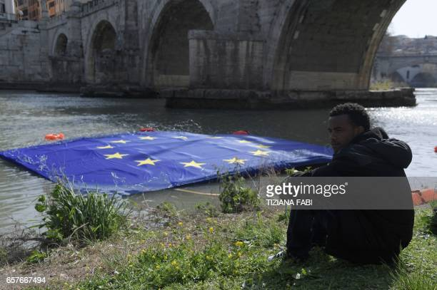 A man sits on the bank of the Tiber river during a symbolic protest of the civil society organizations against the EU's migration policy and to call...