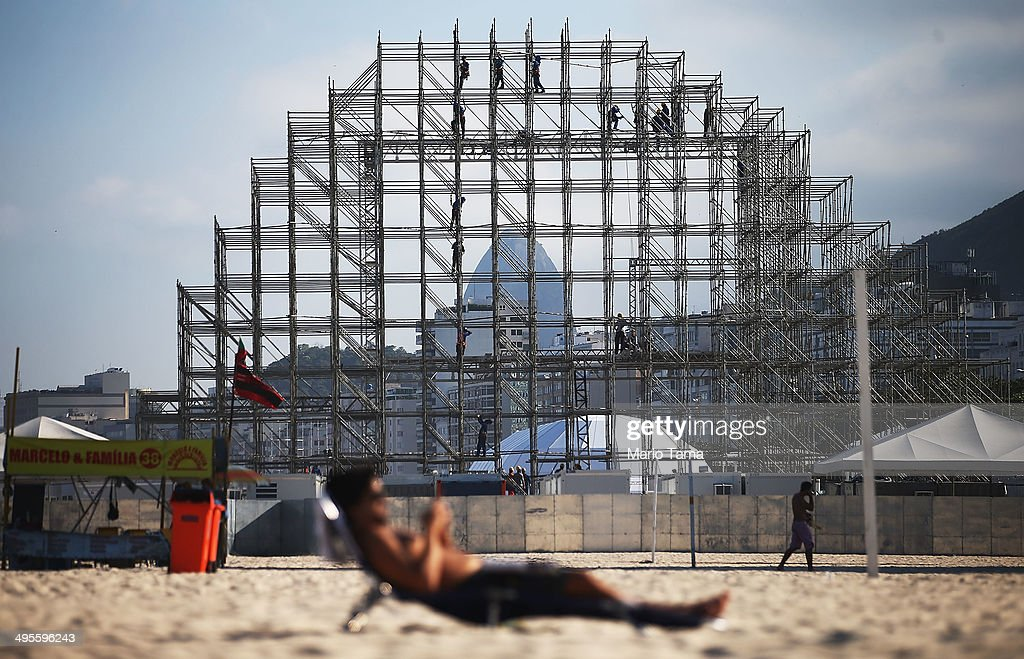 A man sits on the beach as workers construct the FIFA Fan Fest stage, where fans will be able to watch games broadcast live, on Copacabana Beach on June 4, 2014 in Rio de Janeiro, Brazil. Brazil has won five World Cups, more than any other nation. The 2014 FIFA World Cup kicks off June 12 in Brazil.