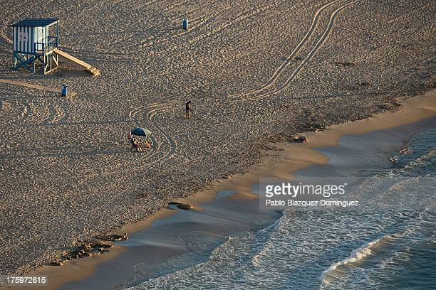 A man sits on the beach while another man searches for metal in the early morning on August 9 2013 in Benidorm Spain Benidorm is one of Europe's top...