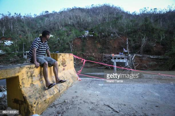 A man sits on the edge of a broken bridge spanning the Vivi River on October 20 2017 in Utuado Puerto Rico The bridge was washed away during...