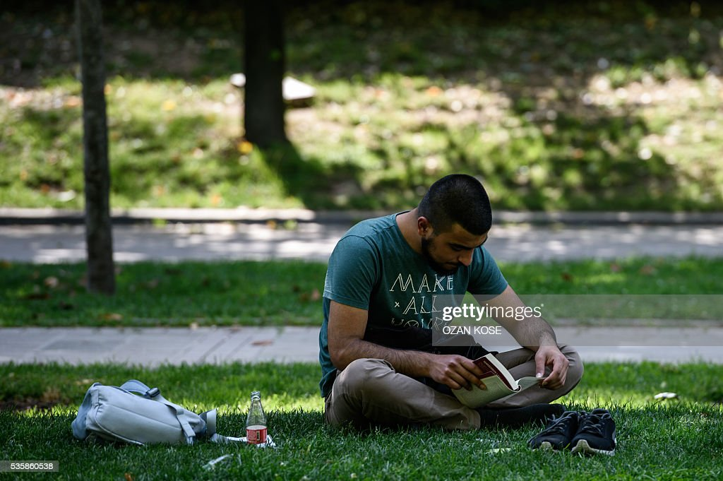 A man sits on the grass and reads a book at the Gezi Park on May 30, 2016 in Istanbul on the eve of the 3rd anniversary of the so-called Gezi Park protests. / AFP / OZAN