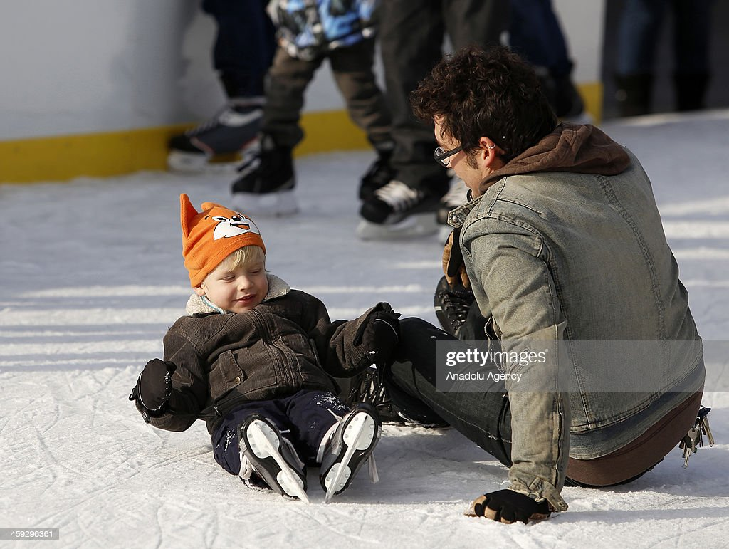 A man sits on the ice after falling down with his child at McCarren Park pool in New York,United States on December 24,2013 after McCarren park pool converted to an ice skating area. Pool hosts 800 visitors everyday, without regard to cold weather American people have fun in McCarren park pool in New York,United States on December 24,2013.