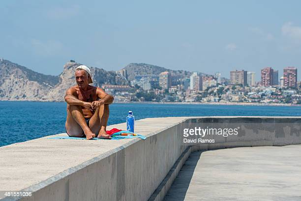 A man sits on the promenade at Poniente Beach on July 22 2015 in Benidorm Spain Spain has set a new record for visitors with 292 million visitors in...
