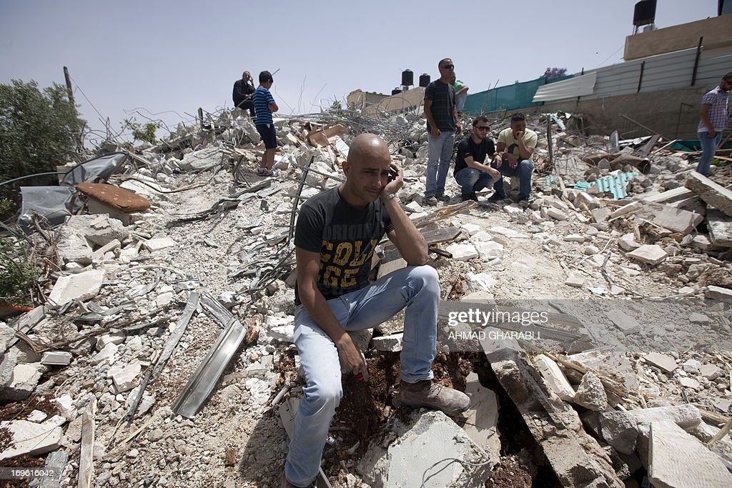 A man sits on the rubble of a Palestinian home after it was torn down by Israeli bulldozers in the Arab east Jerusalem neighborhood of Beit Hanina, on May 29, 2013. Palestinian homes built without a construction permit are often demolished by order of the Jerusalem municipality.