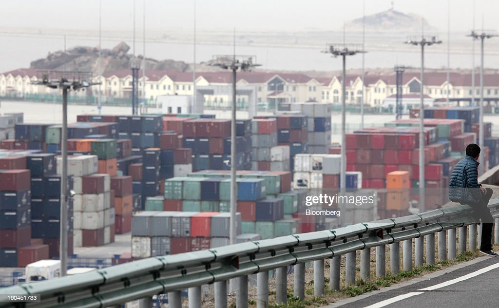 A man sits on the side of a road in front of shipping containers stacked at the Yangshan Deep Water Port in Shanghai, China, on Thursday, Jan. 31, 2013. China's economic growth accelerated for the first time in two years as government efforts to revive demand drove a rebound in industrial output, retail sales and the housing market. Photographer: Tomohiro Ohsumi/Bloomberg via Getty Images