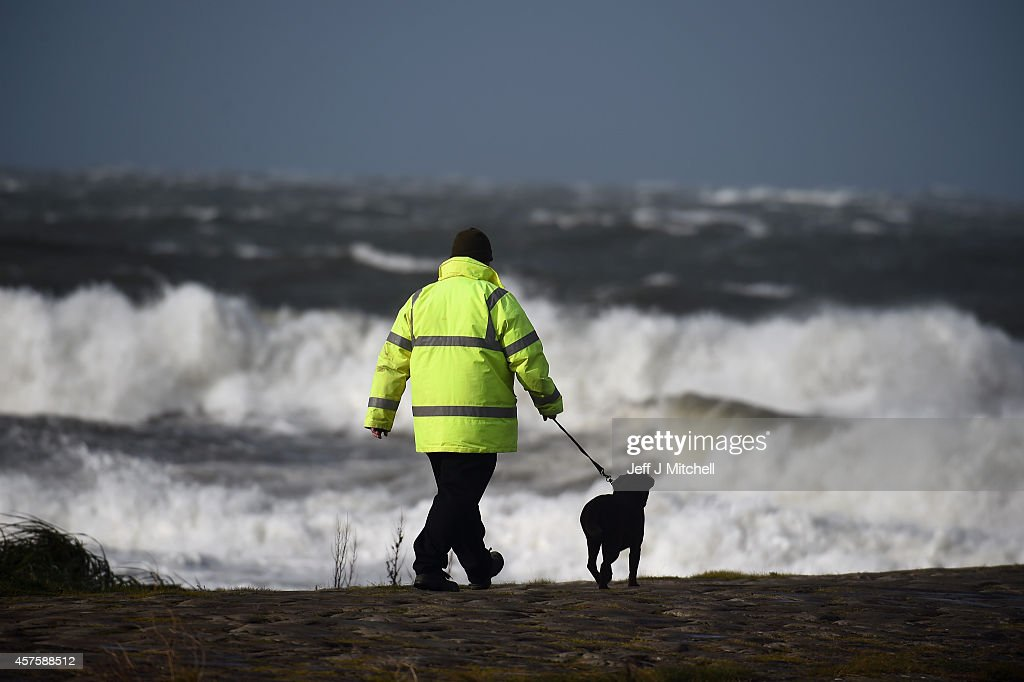 A man sits on the wall of Ballantrae harbour with his dog as the tide comes in on October 21 2014 in Ballantrae ScotlandWeather warnings have been...