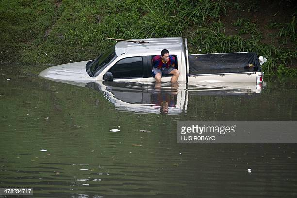 A man sits on the window of his flooded truck in Cali Colombia on March 12 during heavy rains The IDEAM announces a strong rainy season for the next...