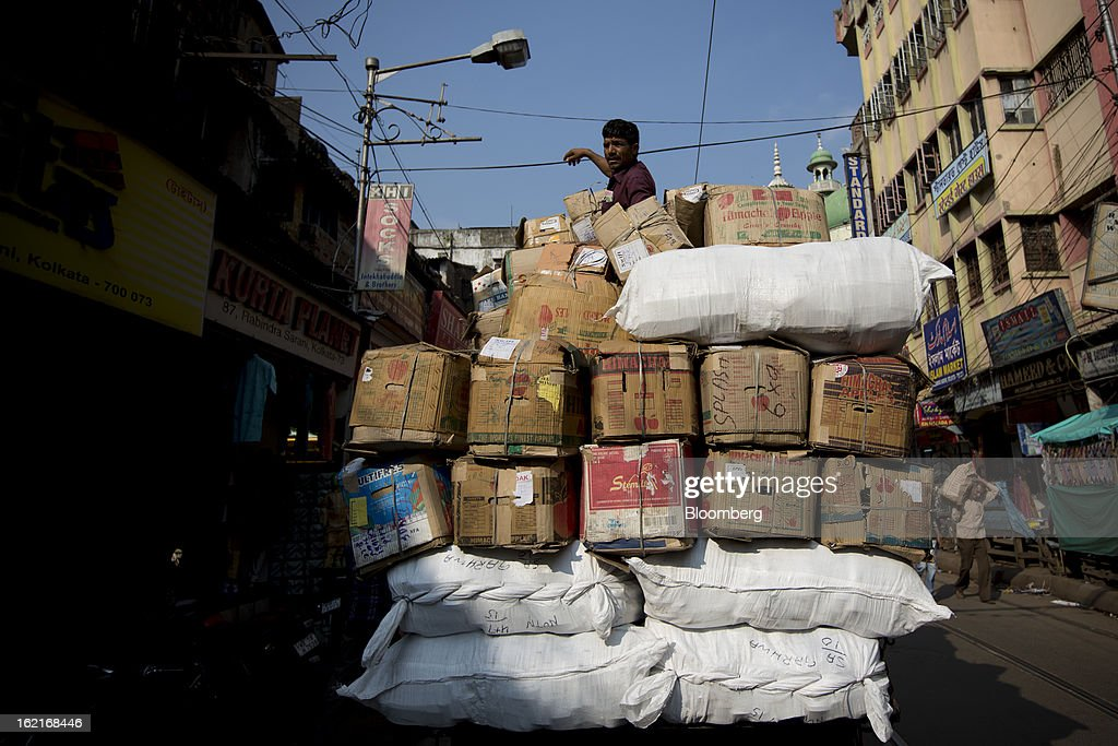 A man sits on top of a truck laden with goods in the Burrabazar area of Kolkata, India, on Tuesday, Feb. 19, 2013. India's slowest economic expansion in a decade is limiting profit growth at the biggest companies even as foreigners remain net buyers of the nation's stocks, according to Kotak Institutional Equities. Photographer: Brent Lewin/Bloomberg via Getty Images