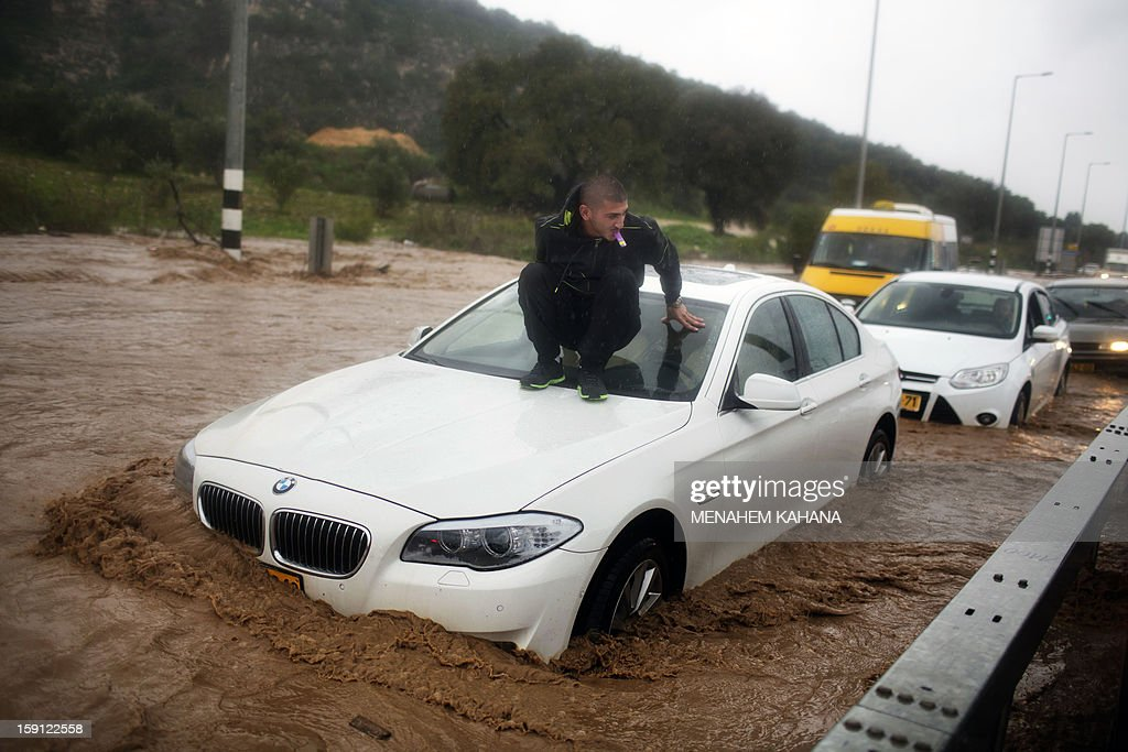 A man sits on top of his car which is stuck in a flooded road near the Israeli-Arab town of Kfar Qara, in central Israel, on January 8, 2013. Stormy weather, including high winds and heavy rainfall, lashed Israel and the Palestinian territories, downing powerlines and trees and blocking roads causing several injuries.