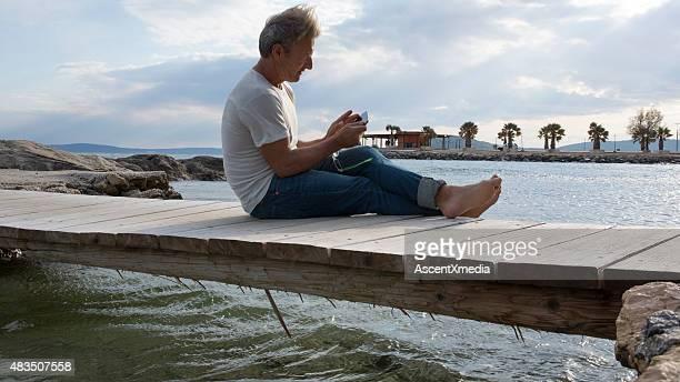 Man sits on wooden bridge above sea,texting