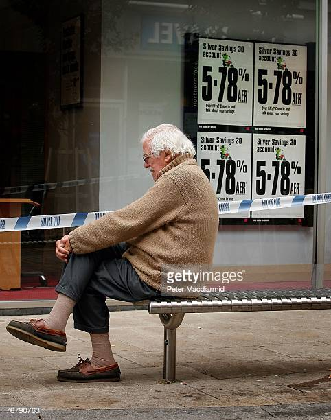 A man sits outside a branch of The Northern Rock bank on September 17 2007 in KingstonUponThames England Approximately 2bn has been withdrawn by...