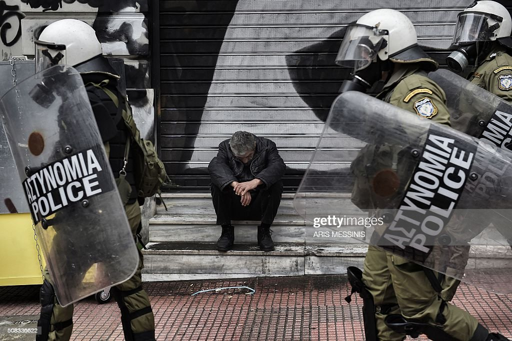 TOPSHOT - A man sits outside a closed store as demonstrators clash with riot police in Athens, on February 4, 2016. Thousands of people marched across Greece on February 4, 2016 as diverse classes united in a crippling general strike over a pension overhaul that has sparked a major backlash against embattled leftist Prime Minister Alexis Tsipras / AFP / ARIS