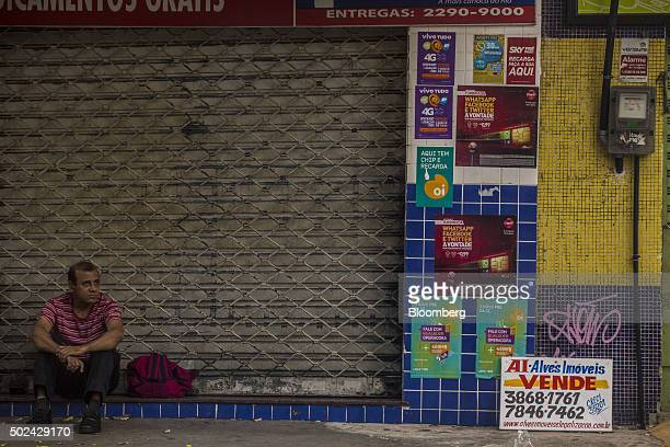 A man sits outside a shuttered business in Rio de Janeiro on Thursday Dec 24 2015 Brazil has slipped deeper into recession with gross domestic...