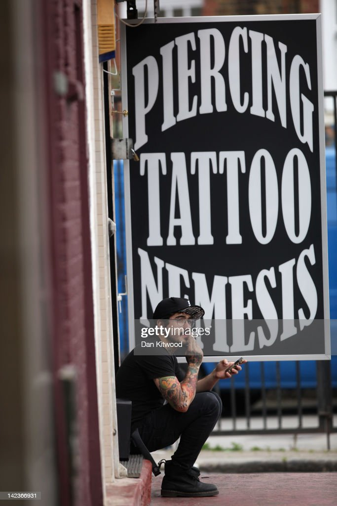 A man sits outside a tattoo parlour in Camden on March 31, 2012 in London, England. Camden in North London has been one of the city's cultural centres since the 1960's, and is home to the famous Camden Market. The borough is rich in musical heritage with a variety of musical and comedy venues, theatres and art galleries.
