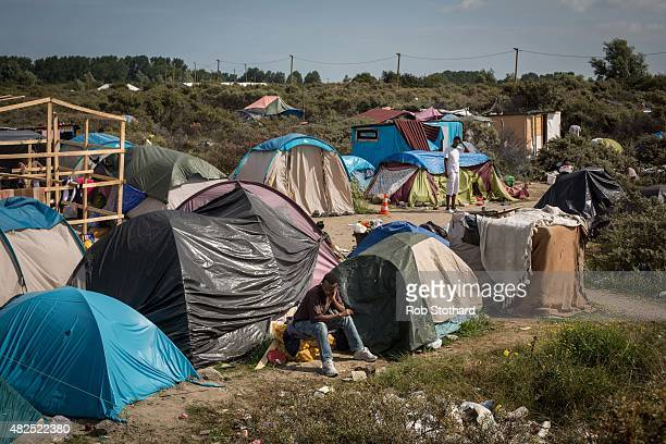 A man sits outside tents in at a make shift camp near the port of Calais on July 31 2015 in Calais France Strike action and daily attempts by...