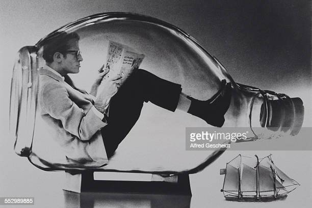 A man sits reading a newspaper in a large glass bottle replacing the model ship 1994