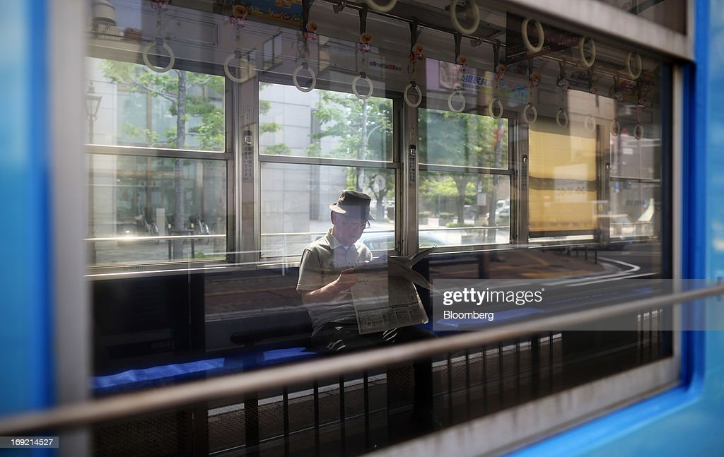 A man sits reading a newspaper on a tram in Okayama, Japan, on Tuesday, May 21, 2013. The Bank of Japan, forecast to maintain plans for expanded monetary easing at a meeting ending on May 22, is targeting 2 percent inflation in two years after more than 10 years of entrenched deflation. Photographer: Tomohiro Ohsumi/Bloomberg via Getty Images